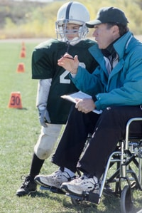 Man in wheelchair coaching a young football player.