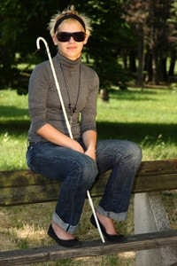 Smiling young blind woman sitting on a fence.