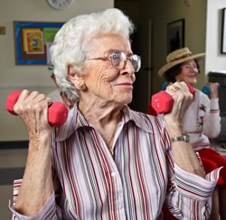 Elderly woman exercising with hand weights.