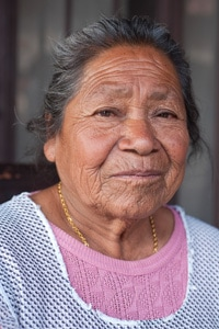 Elderly Native American Woman in a pink shirt.